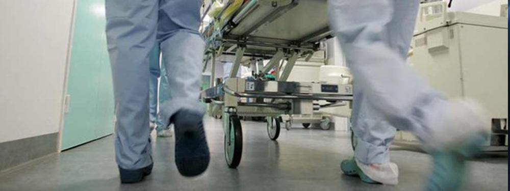 Photo de personnel hospitalier courant dans les couloirs d'un hopital poussant un charriot
