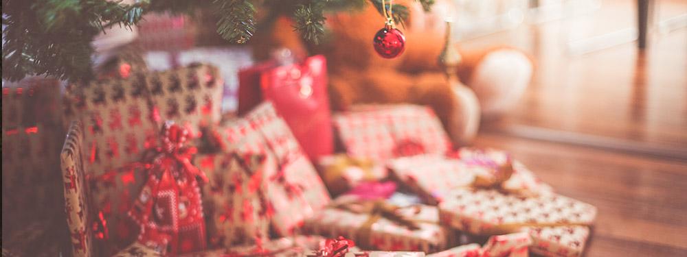 Photo de cadeaux posés au pied d'un sapin de Noël