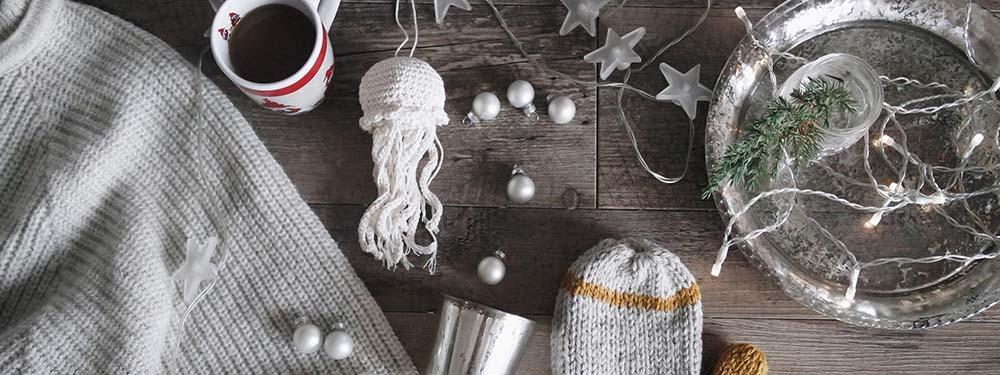 Photos de pull, ants , de pelotes de laine, guirlande de Noel posés sur une table