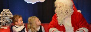 Photo du Père Noël assis sur un canapé rouge avec 2 enfants qui le regardent
