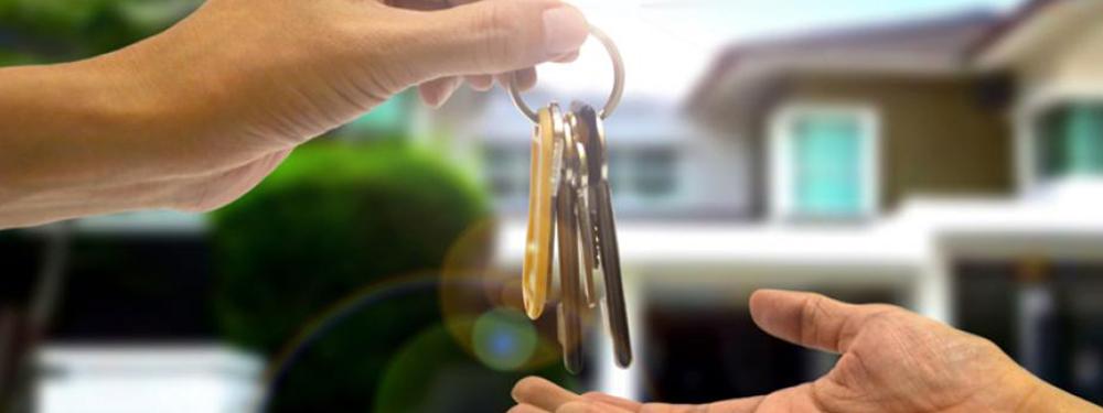 Photo d'une main donnant des clefs à une autre devant des maisons