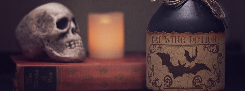 Photo d'une bouteille de poison avec des chauve-souris dessus avec en fond un crâne et une bougie
