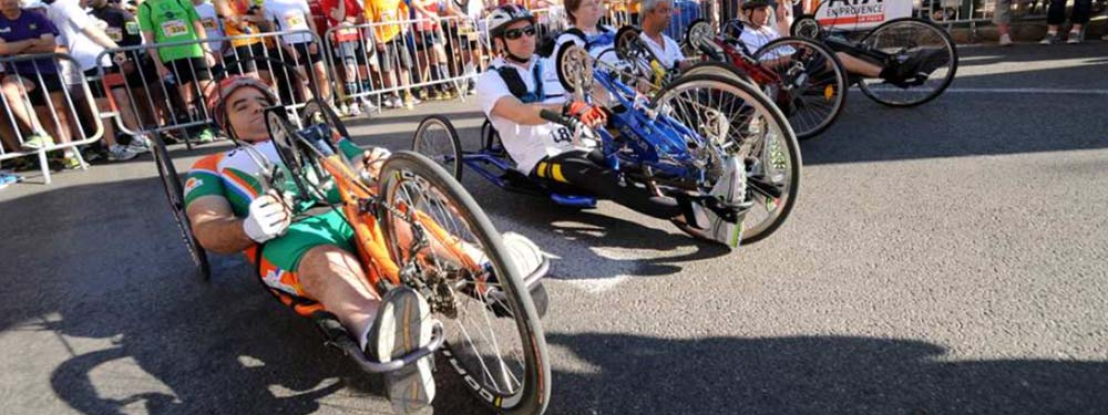 Photos de 5 personnes en situation de handicap sur des vtt adaptés prêt à s'élancer sur une course