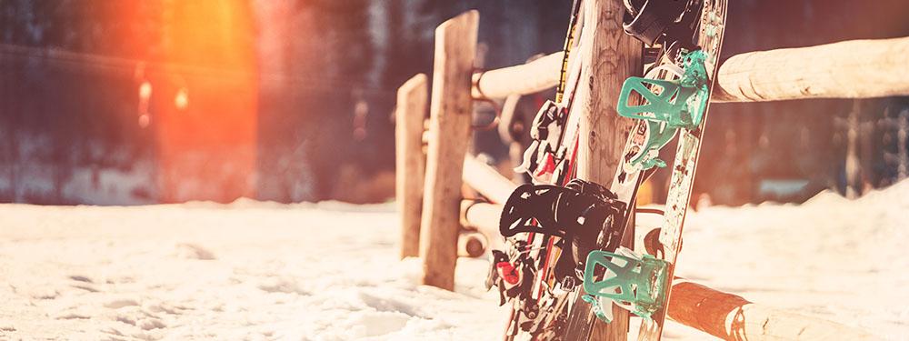 Photo de skis et de snows plantés dans la neige et posés sur une balustrade en bois