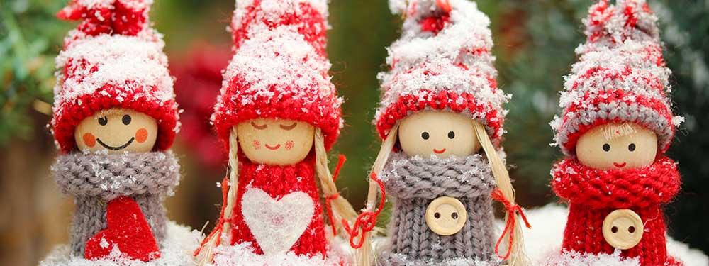 Photo de 4 bonhommes en bois avec bonnet et pull en laine sous la neige