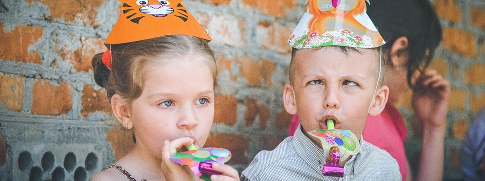 Enfants portant des chapeaux de fête et des cotillons, un garcon en train de loucher et une fille concentrée
