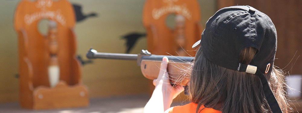 """Photo d'une fillette en train de tirer à la carabine lors du """"jeux mai'clate"""""""