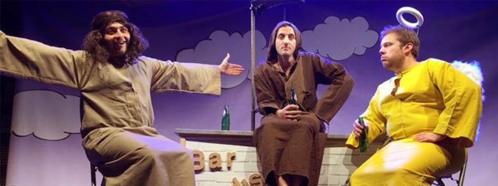 Photo montrant les 3 acteurs sur scène habillés en anges et en démons accoudés à un bar et buvant de la bière