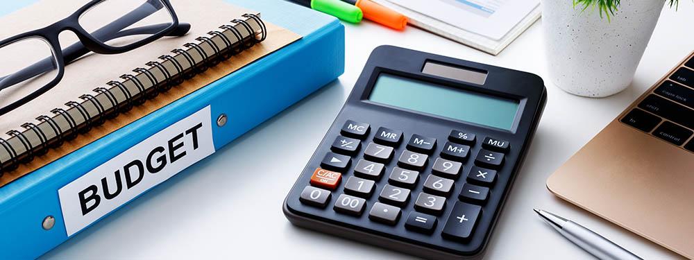 """Photo d'un bureau avec posé dessus une calculatrice, un ordinateur, des dossiers """"Budget"""""""