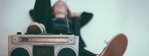 Photo d'une radio des années 90 en premier plan avec une femme floutée au 2e plan allongé sur le sol, le pied posé sur la radio