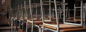 Photo montrant des chaises mis à l'envers sur des tables dans une classe d'école