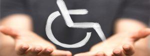 Photo d'un jeune homme main tendue paumes vers le haut avec le dessin représentant la signalisation des personnes en situation de handicap