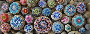 Photo de galets peints avec des décorations type mandalas de toutes les couleurs