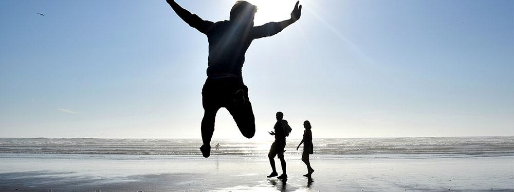 Photo d'un homme en train de sauter au bord d'une plage