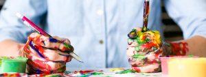 Photo d'un homme les mains pleines de peintures, un pinceau dans une main et un crayon dans l'autre
