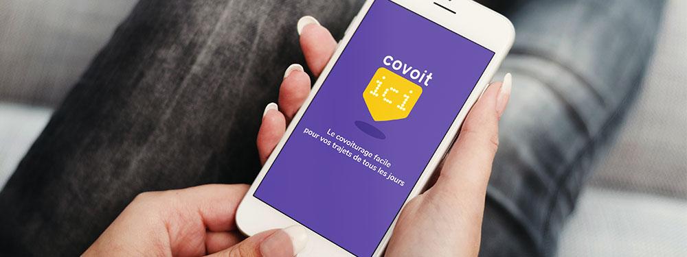 Photo d'une femme assise tenant dans ses mains un téléphone ouverte sur l'application Covoit'ici