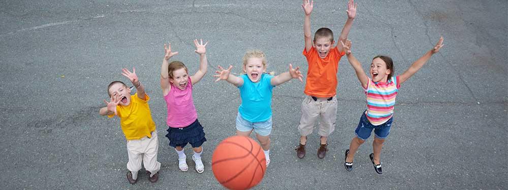 Photo d'un groupe d'enfant ravis de jeter un ballon de basket en l'air