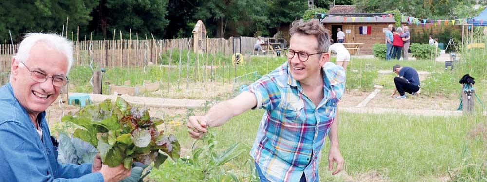 Photo de couverture du Vmag montrant 1 homme en train de rire donnant une salade à un autre au milieu du potager partagé de la touloubre