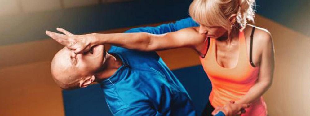 Photo d'une femme en train de donner un coup dans le nez d'un homme marquant des cours de self défense