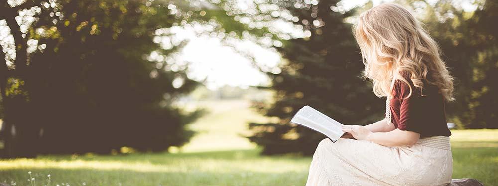 Photo d'une femme en train de lire dans un prairie