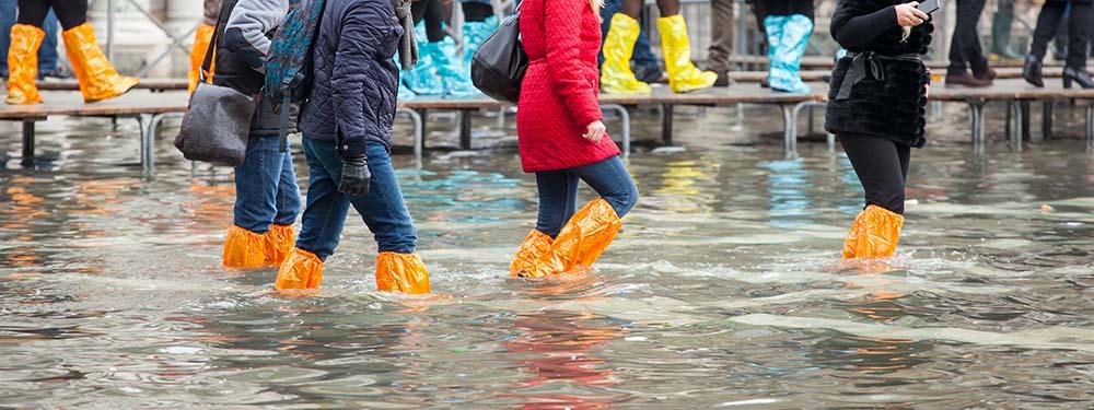 Photo de 4 filles marchant dans les rues remplies d'eau dû à une inondation