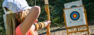 Photo montrant 1 jeune fille visant une cible au tir à l'arc