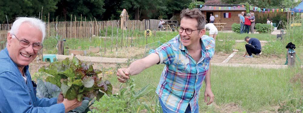 Photo d'un homme tout sourire donnant une salade à un autre homme au milieu du potager partagé de la Touloubre