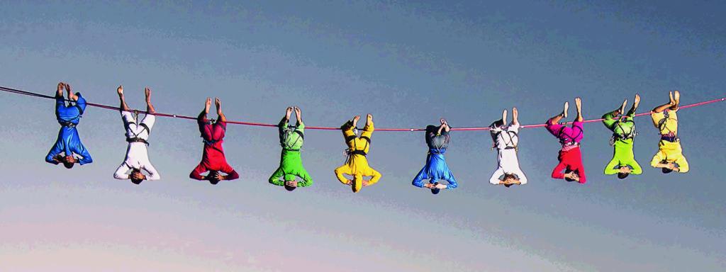 Photo représentant 10 personnages en kimonos colorés suspendus par les pieds à une corde à linge
