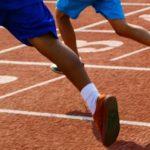 Photo de jambes d'enfants en train de courir sur une piste d'athlétisme