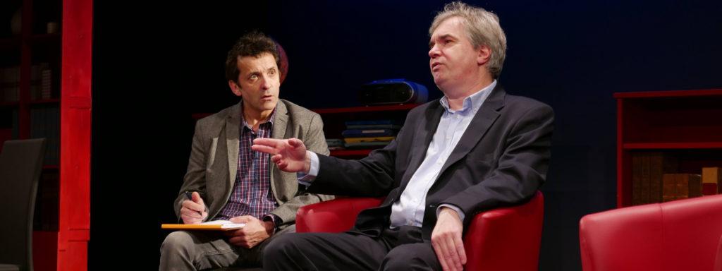Photo représentant un psychologue et son patient en pleine séance. Les deux personnages sont assis sur des canapés rouges, à gauche, le psychologue prend des notes, à droite le patient parle en faisant des gestes