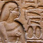 Photo représentant un mur sur lequel est gravé un pharaon entouré de hiéroglyphes