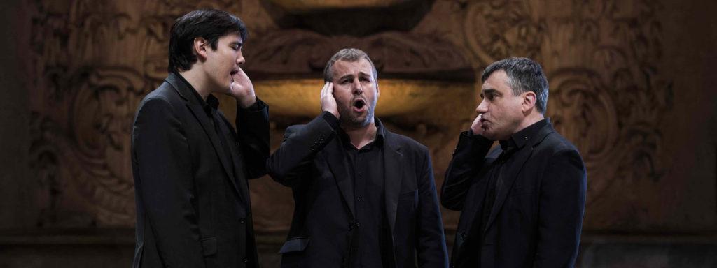 Photo représentant 3 chanteurs de polyphonies corses dans une église, en train de chanter, chacun la main sur l'oreille