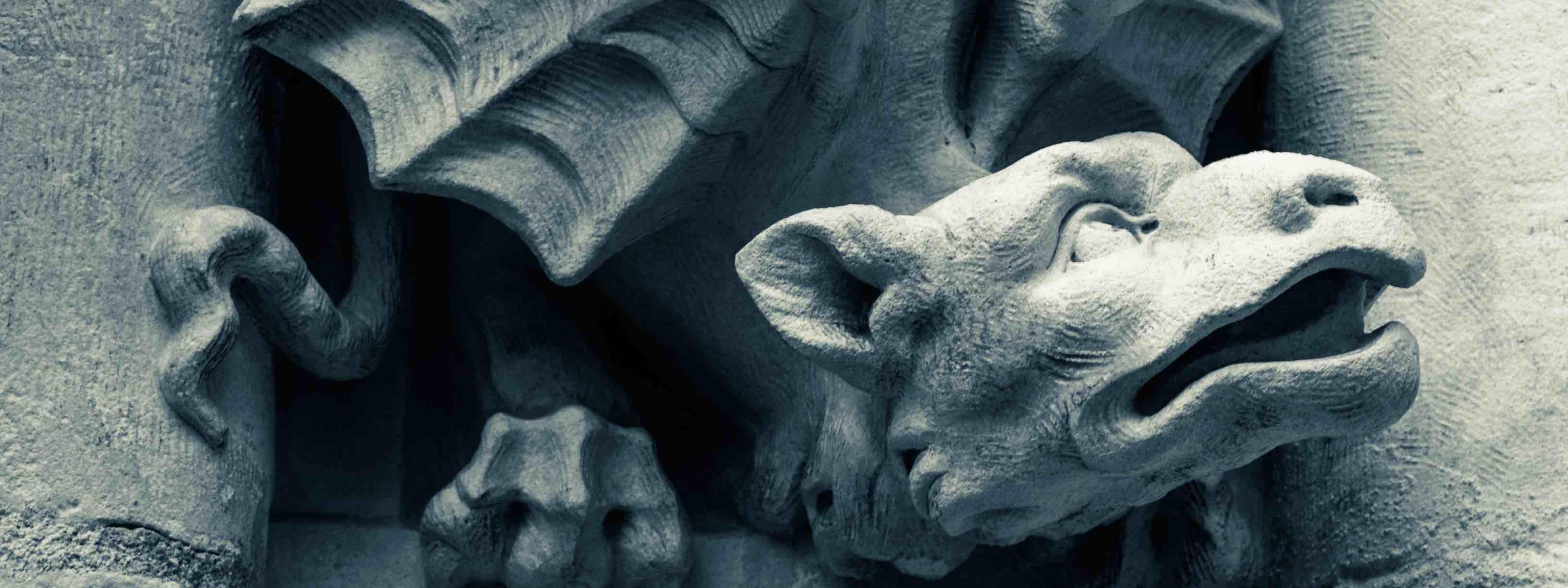 Photo représentant une sculpture en pierre de dragon. Le dragon est recroquevillé et regarde en l'air, bouche ouverte