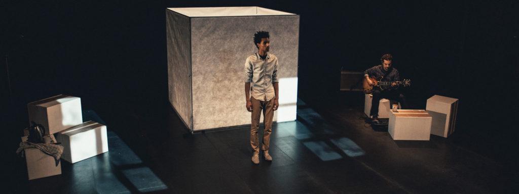 Photo représentant un homme vêtu d'une chemise et d'un pantalon devant un carré blanc lumineux. À sa droite, un guitariste, vêtu d'une chemise noire est assis.