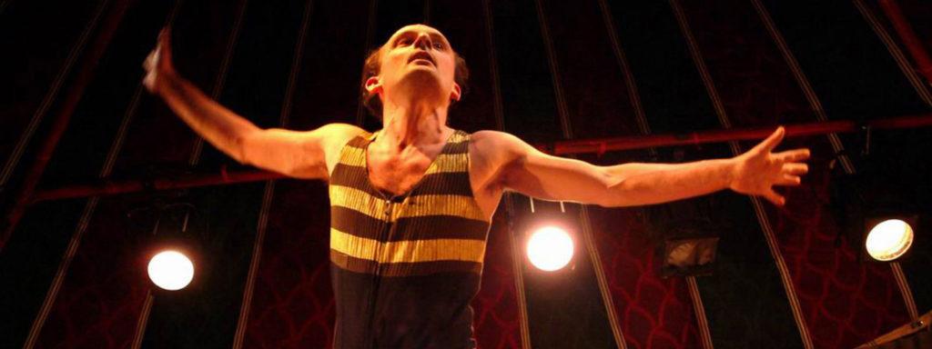 Photo représentant un comédien sous les projecteurs les deux bras ouvert, portant un costume noir et jaune à rayures