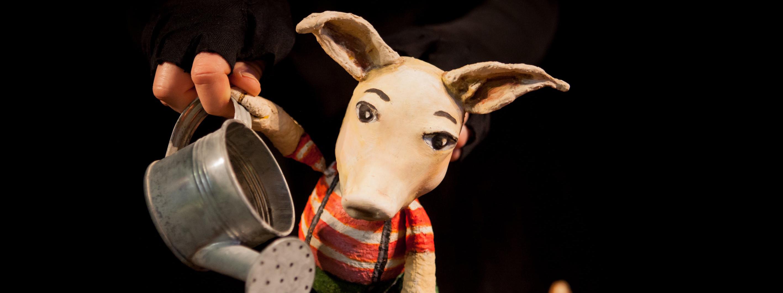 Photo représentant une marionnette cochon qui tient un arrosoir