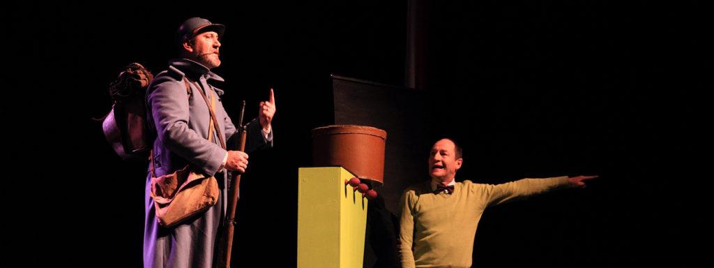 Photo représentant 2 hommes : 1 professeur vêtu d'un pull vert pointant son doigt vers la droite et un soldat de la première guerre mondiale en uniforme