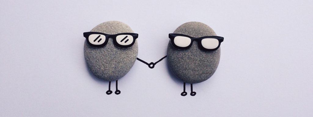 Photo montrant 2 galets portant des lunettes de soleil et se tenant la main, mains dessinées au stylo