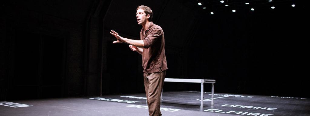 Photo représentant un comédien au milieu de la scène en pleine élocution. Au sol, les noms des différents personnages sont écrits en grandes lettres blanches