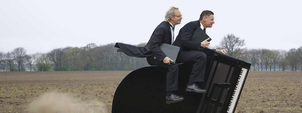 Photo représentant deux musiciens classiques en smoking chevauchant à toute allure un piano dans un champ