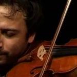 Photo représentant un violoniste en train de jouer les yeux fermés