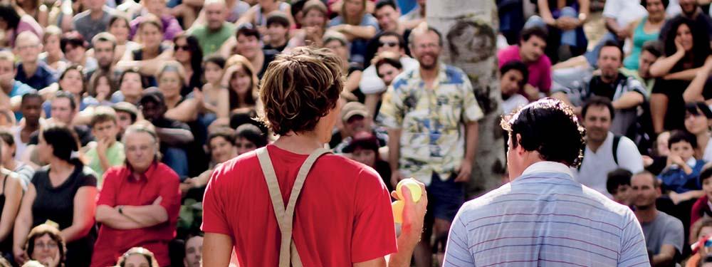Photo montrant une compagnie de cirque de dos devant un public