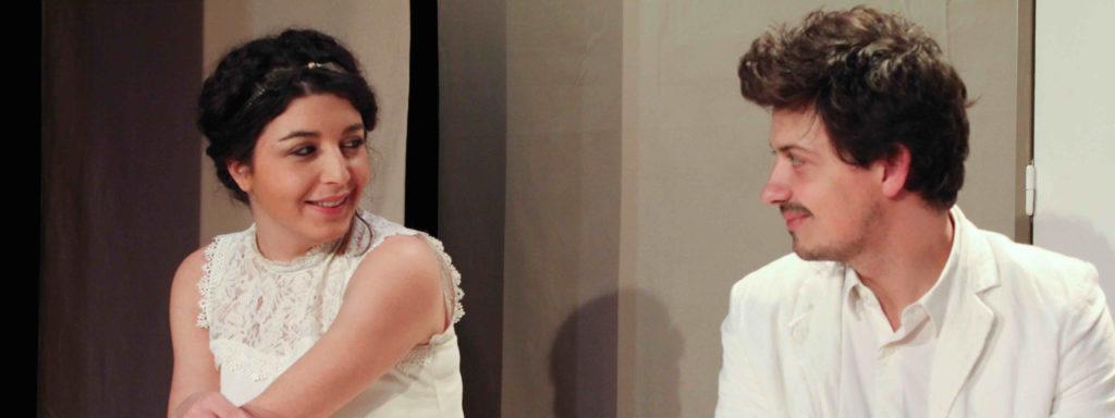 Photo représentant une femme en robe de mariée et un homme en costume blanc se regardant avec complicité