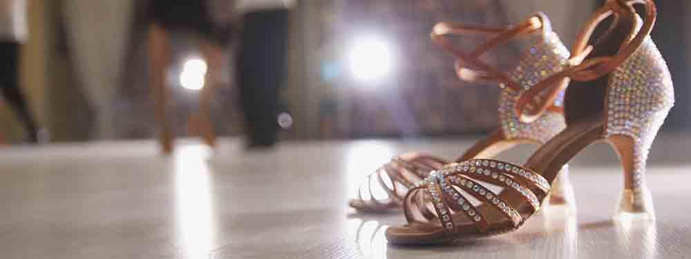 Photo d'une vue du sol d'une salle de danse avec un premier plan une paire de chaussures à strass