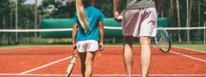 Photo d'une jeune joueuse de tennis en train de marcher sur un court à coté de son professeur