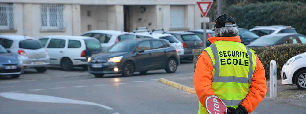 """Photo d'un bénévole """"Volontaire école"""" aidant à faire traverser les petits Venellois"""