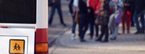 Photo de l'arrière d'un bus scolaire avec en ée plan des enfants sur le parvis de l'école