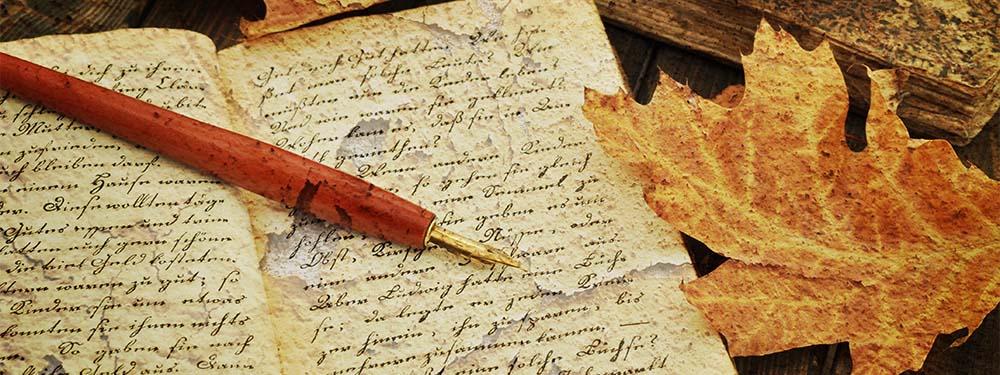 Photo d'un vieux cahier ouvert avec un stylo plume posé dessus et des feuilles aux couleurs d'automne