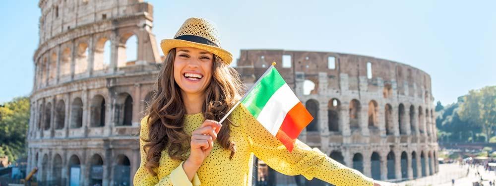 Photo d'une femme en train de sourire devant le colisée en Italie portant un drapeau italien à la main