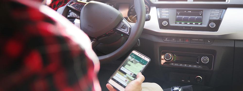 Photo d'un homme au volant regardant ses sms sur ton téléphone